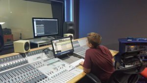 One of the participants using the mixing desk within the recording studio